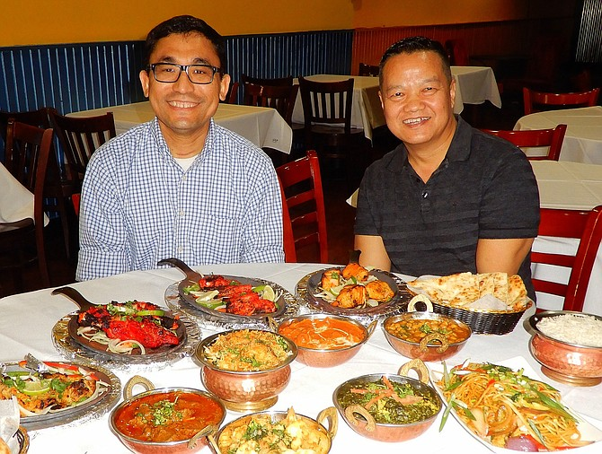 From left, are Raj Tamang and Shyam Lama with a sampling of the colorful and tasty dishes at Tandoori Nights.