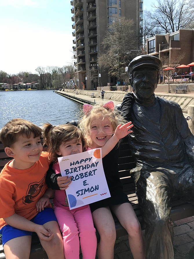 The Kooy children, Grant, 4, Eve, 2, and Ashton, 6, hold up a birthday wish sign for Reston's founder, Robert E. Simon, to celebrate 2019 Founder's Day. Melissa Romano, the owner of Lake Anne Brew House and Nordic Knot on the Plaza, made the birthday greeting sign for the special occasion.