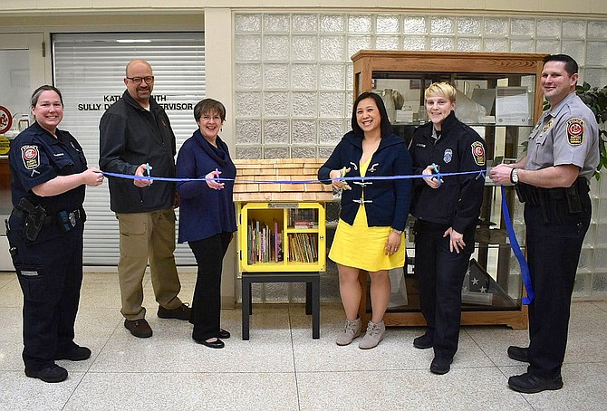 Cutting the ribbon for the Little Free Library are (from left) MPO Sherry O'Brien, retired MPO Denny Vorbau, Kathy Smith, Southita Brower, PFC Meg Hawkins and Lt. Todd Billeb.