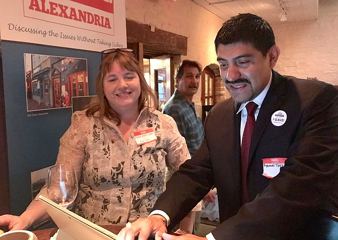 Agenda:Alexandria executive director Donna Walker James, left, watches as Fernando Torrez makes a donation to the organization at an early giving Spring2ACTion Happy Hour April 8 at Union Street Public House.