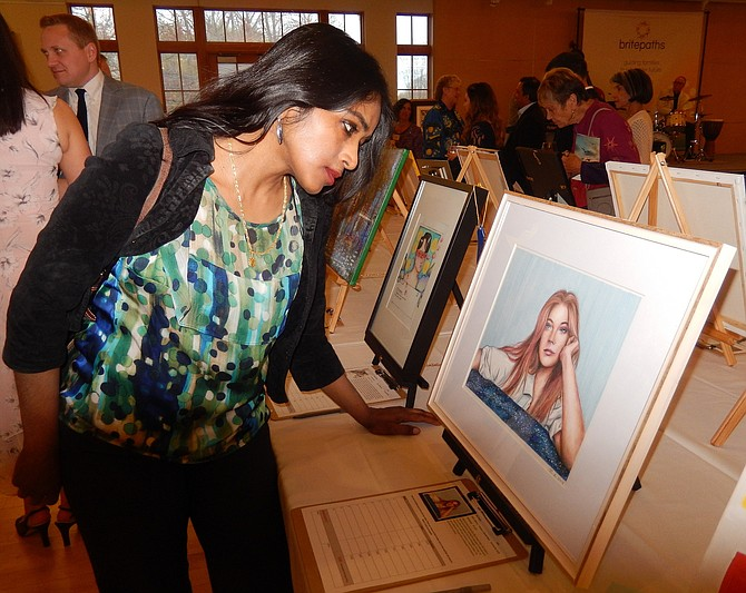 """Shobha M. looks closely at a painting at last year's """"Artful Living."""""""