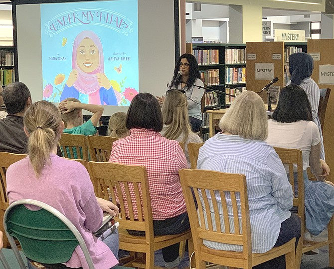 More than eighty children, teens and adults listen to remarks by children's author Hena Khan at the Reston Regional Library.