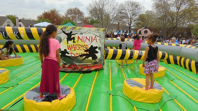Children jump in the Ninja Warrior Inflatable ride.