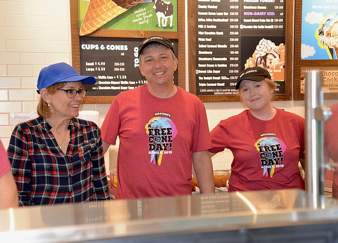 "The Vienna Ben & Jerry's owner Kyle Hosch had lots of willing assistants on Free Cone Day, like Carol Hamal (left), a volunteer with local nonprofit Committee for Helping Others (CHO). CHO was the designated charitable organization that Hosch called the ""perfect partner"" to benefit from donations made during the event. On the right is scooper extraordinaire and B & J's employee Moira Harris."
