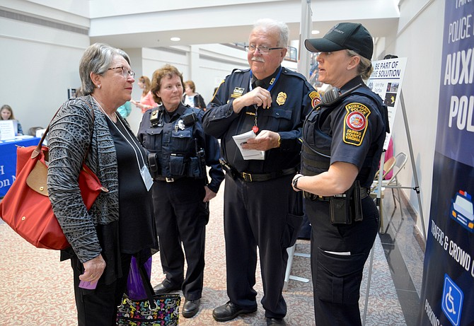 "Auxiliary Police Officers, from left, Nina Aldrich, Fred Sanborn, and Ashley Soloff, were at the NoVa Positive Aging and Wellness Fair looking for recruits. Here they are working hard to convince Burke resident Dorothy Keenan to join their ranks. So – did they recruit Keenan? Probably not, since she is the ""Champion"" and leader of busy nonprofit ""GrandInvolve."""