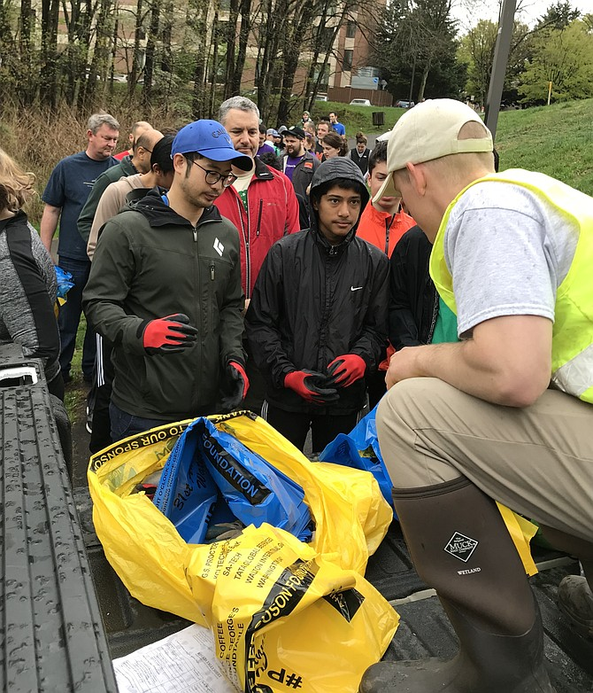 Garrett Stewart, watershed specialist with the Reston Association, distributes recycling and trash bags to volunteers during the 31st Annual Potomac River Watershed Cleanup coordinated by the Alice Ferguson Foundation and Reston Association.