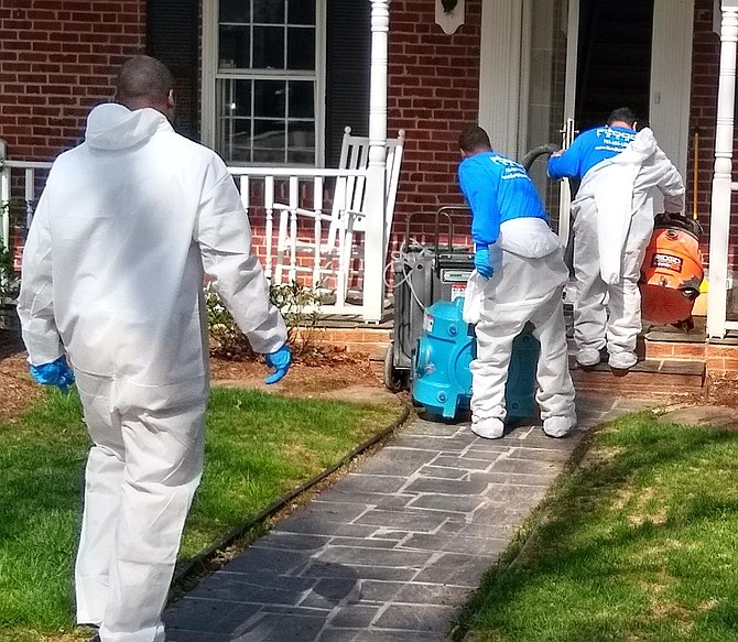 "Restoration company employees in ""moon suits"" arrive to clean out basements filled with sewage from overflow on N. Powhatan Street on April 7."