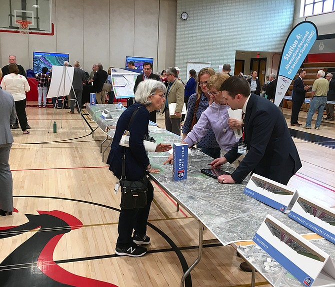 Scores of people attending the workshop on proposals to widen the Beltway and I-270 spread out at different exhibits around the cafeteria of Pyle Middle School in Bethesda.