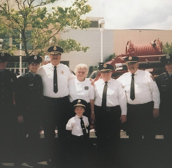 Long-time Cabin John Park Volunteer Fire Department Auxiliary President Mary Morgal, center, is flanked by former Chief James Seavey, left and Kathy Donahoe, right at the annual Maryland State Fireman's Association convention. In front is her great-grandson.