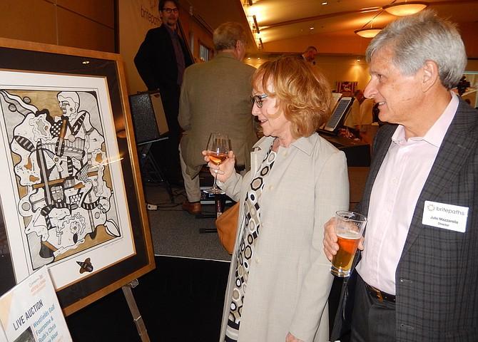 Kim and Julio Mazzarella peruse the artwork during last year's event.