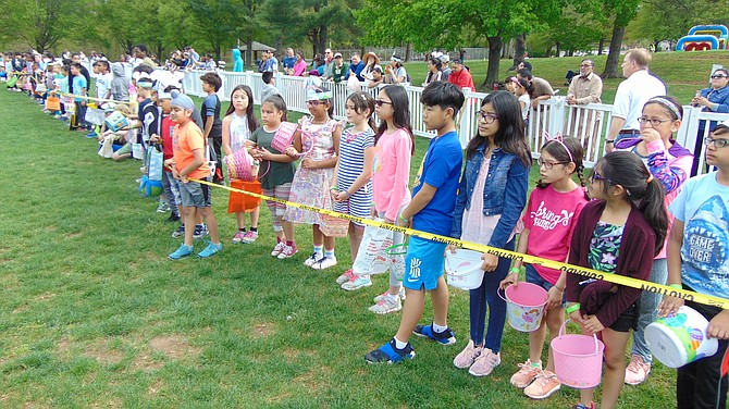 Children in the 9-10 age group wait for the Easter Egg Hunt to begin at Van Dyck Park in Fairfax.