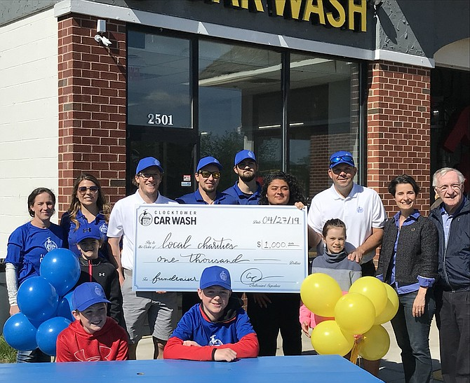 Clocktower Car Wash co-owners, Tim Ferraro and Gus Kearney, present a check for $1,000 to local charities during the business's inaugural Spring Community Festival as (far right) State Senator Jennifer Boysko (D-33), Delegate Ken Plum (D-36) and others join in the fun.