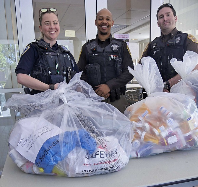 From left: Corporal Sarah Butzer, Deputy Dominique Smith and Corporal Andrew Flowers fill bags with prescription drugs at Prescription Take-Back day Saturday, April 27.