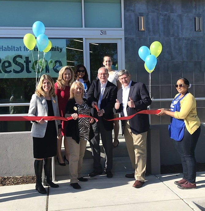 Jon Smoot, Executive Director of Habitat NOVA cuts the ribbon signifying the official opening of Herndon ReStore at 311 Spring Street, Herndon. With him, Herndon Councilmember Jennifer Baker, Vice Mayor Sheila Olem and Supervisor John Foust (D- Dranesville) and other supporters look on.