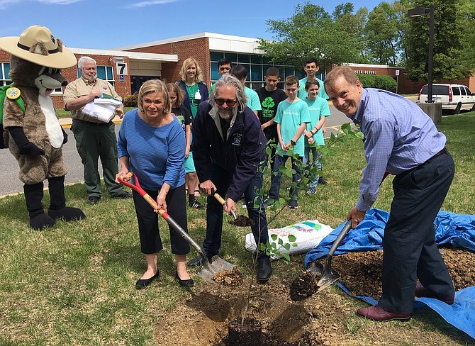 From left, Council members Janice Miller and Michael DeMarco, plus Mayor David Meyer, dig a hole for the redbud tree.