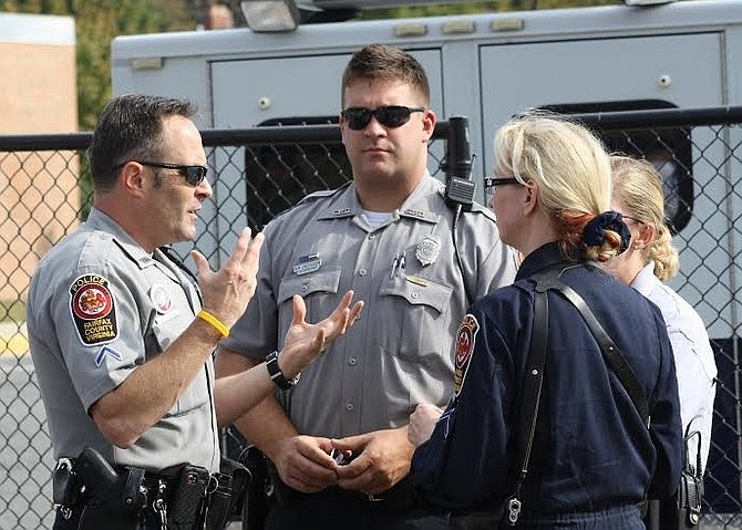 Ryan Lindenbaum (center) on the job, conferring with other police officers.
