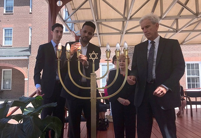City Councilman Mo Seifeldein lights one of six candles of a candelabrum as state Sen. Dick Saslaw (D-35) looks on during the 32nd annual Days of Remembrance of the Victims of the Holocaust Ceremony of Commemoration May 2 in Market Square.