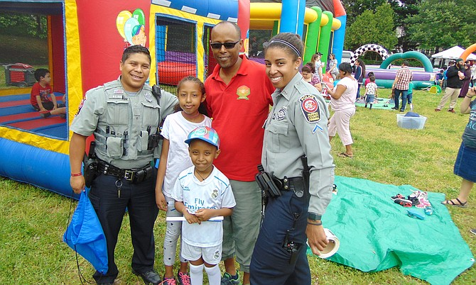 Officers Bayron Gudiel and Melanie Todd of the Franconia District Police Station with the Fitsume family of Lorton:  Girma, Nehemiah, 6, and Netanya, 9, at the Hope and Health Festival in Lorton on Saturday.
