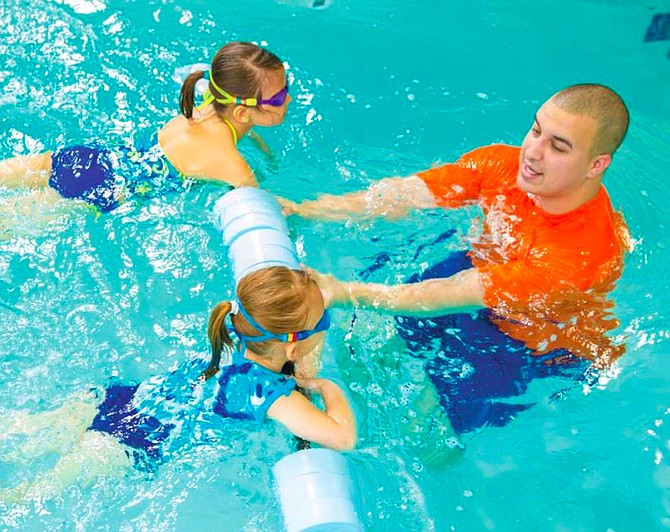 An instructor at Goldfish Swim School teaches young children how to swim. Lessons can help ensure water safety.