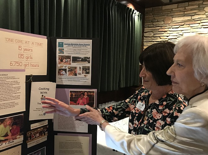 Leslie Tourigny, American Association of University Women (AAUW) of Virginia Co-President, and Dianne Mero, AAUW Reston-Herndon Area President, look over one of the historical displays presented at the organization's 50th Anniversary Celebration Luncheon.