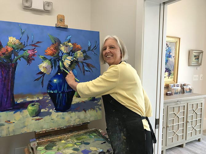 Trisha Adams paints in her newly opened art gallery/studio located at 708 Elden Street, Suite A.