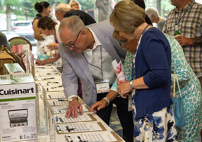 Attendees review auction items at the Culpepper Garden 2018 Springtime Party.
