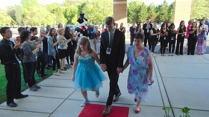 Andrew Valentine (center) escorts Gracie Craun and Andrea Cappello down the red carpet at the Joy Prom.