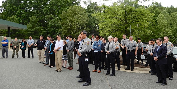 Police officers and others bow their heads during the moment of silence. At far right, in suit, is Deputy County Executive Dave Rohrer.