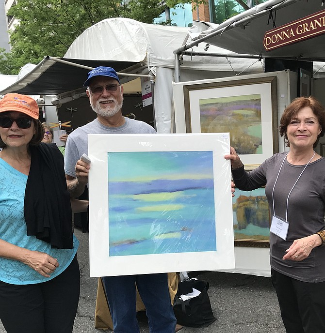 "Patron Jean Reynolds of Reston with husband, Jim: ""We come to the Fine Arts Festival every year. I was drawn to this work because of the beautiful pastels."" Drawing Artist Donna Grande of Montclair, New Jersey: ""This is my fourth time juried in, and it is always a fabulous show."""