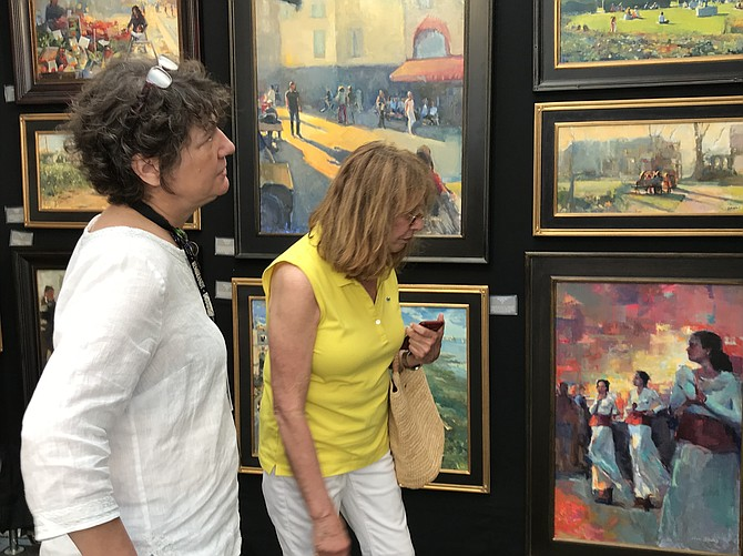 Meg Hill of Reston admires the impressionist oil paintings by award-winning local artist Jill Banks of Fairfax during the 2019 Greater Reston Arts Center Northern Virginia Fine Arts Festival.