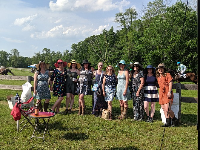 As the horses run by in the background, tailgaters at the Potomac Hunt Races enjoy the day. From left, Patty Sims, Suzannah Cornue, Megan Aprill, Natalie Hollis, Christine Raymer , Kathy Savory, Lara Schwartz, Cyndi Hill, Chelsea Eldridge, and Abigail Fulmer, from Destination Eventing and Miles Ahead Farm.
