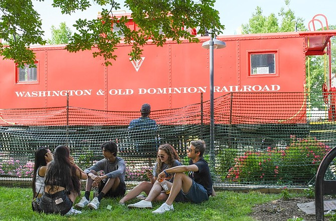 Young adults sit under the shade by the red caboose.