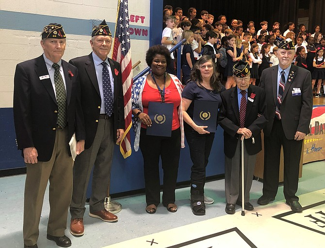 Lyles-Crouch Traditional Academy kindergarten teacher Wanda Allen and principal Dr. Patricia Zissios, center, stand with members of American Legion Post 24 after being honored for their efforts to promote patriotism at the school's May 24 Memorial Day program. With Allen and Zissios are Henry Dorton, Post 24 Commander Doug Gurka, WWII veteran Col. Kim Ching and Jim Glassman.