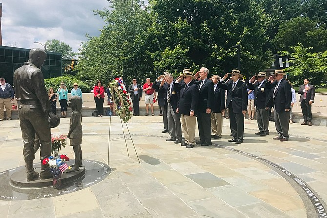 "Members of the United States Military Academy class of 1959 salute after placing a wreath at the statue of classmate Humbert ""Rocky"" Versace during the Memorial Day Ceremony May 27 at the Captain Rocky Versace Plaza and Vietnam Veterans Memorial in Del Ray."