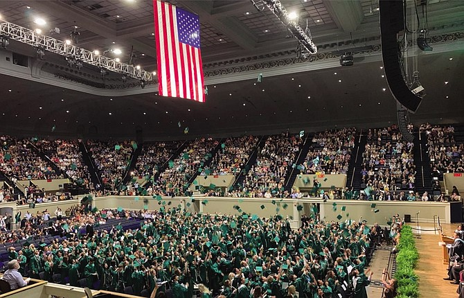 Students of Langley's Class of 2019 toss their graduation caps into the air to celebrate their certification as official graduates.