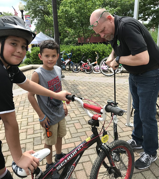 "Volunteer Dave Meyer, co-owner of Green Lizard Cycling in Herndon, pumps up the tire for Edvin Orellan, 6, of Herndon at ""Play It Safe: Bike Rodeo and Safety Fair"" presented by Herndon Parks and Recreation."