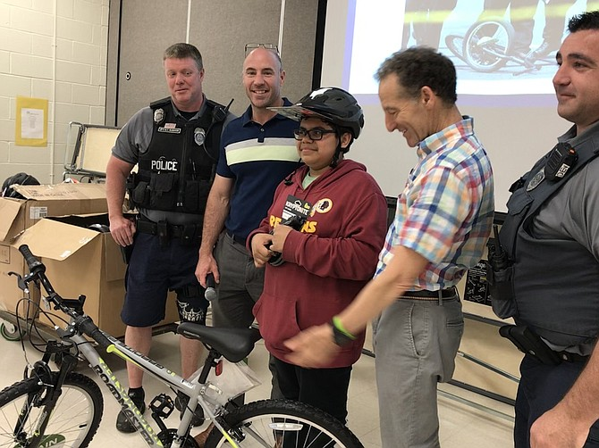 FCPD officers of Reston District station, MPO B.T. McMahon and PFC D. Rocco, along with Raymond Lonnett, Principal, Hutchison ES and Attorney Doug Landau, present Jorge Arce, 12, student at Hutchison Elementary School, with the bicycle he won during Landau Law firm's Lids on Kids program held May 22.