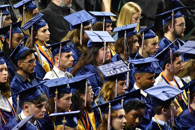An embellished graduation cap sticks out in a sea of blue.