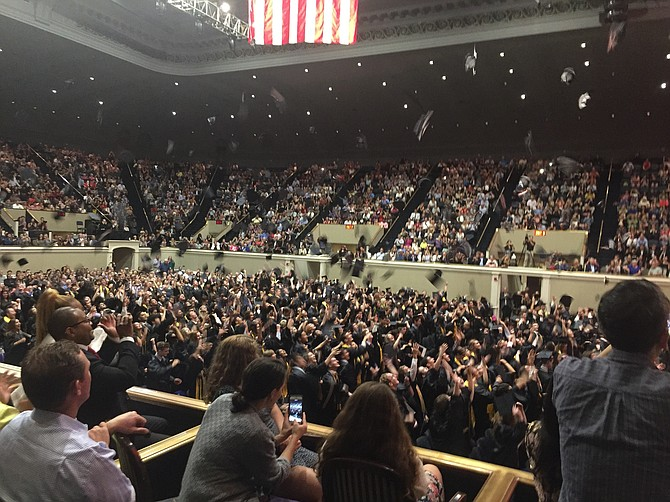 Graduates throw their caps in the air in celebration.
