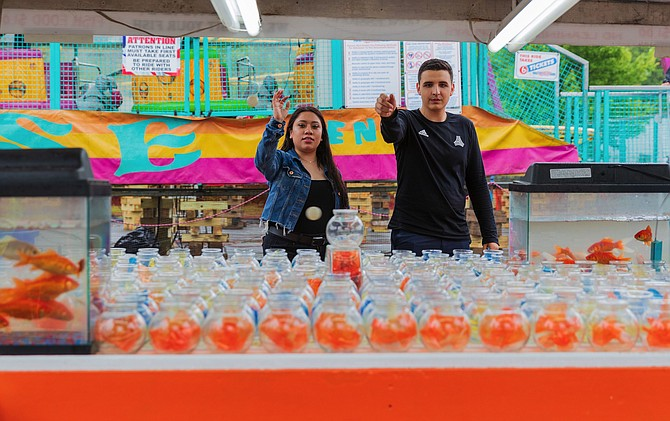 Philip Perez-Avalos and Aileen Bazan from Fairfax show off their ping pong ball throwing skills by winning five fish.