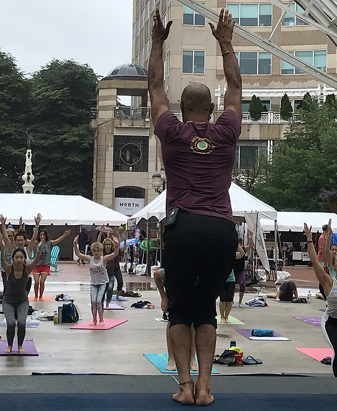 A yoga instructor teaches a free class as one of the activities held throughout the day at Love Your Body Yoga Festival, Reston Town Center, Sunday, June 9.
