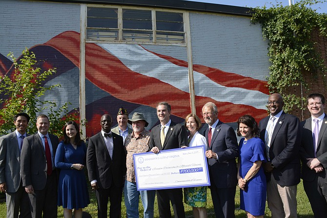 State and local officials hold up the representative $700,000 check for the new veterans' housing project on Washington Blvd. From left: Kevin Yam, APAH board chair; Del. Patrick Hope, Katie Cristol, Arlington County Board; Carlos Hopkins, secretary of Veterans and Defense Affairs for the Commonwealth of Virginia; Bill Fahey and Dan Donahue, American Legion Post 139; Gov. Ralph Northam; Nina Janopaul, APAH president and CEO; John Milliken, APAH board member; state Sen. Barbara Favola; Christian Dorsey, Arlington County Board Chair; and Erik Johnston, director of the Department of Housing and Community Development for the Commonwealth of Virginia.