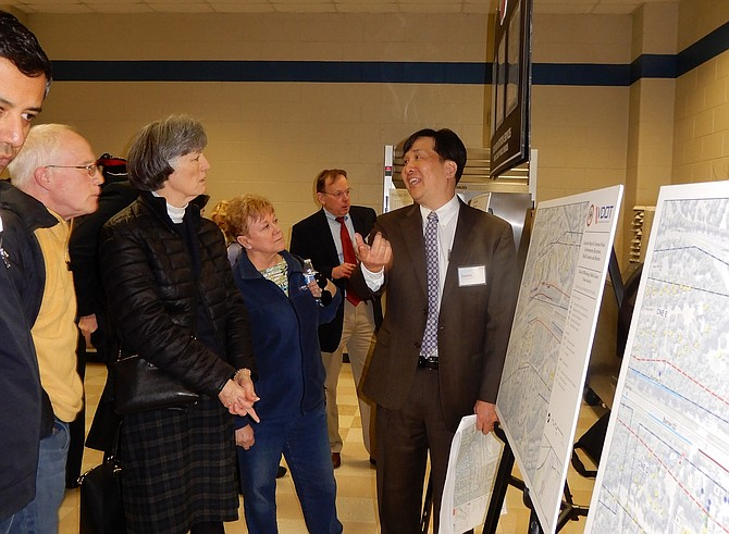 Jason Yazawa (on right), a project consultant, talks to meeting attendees.