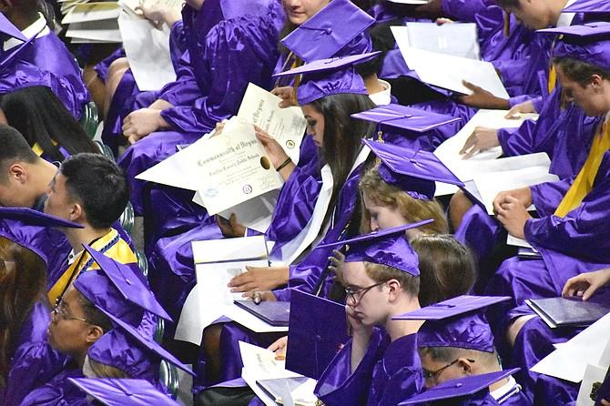 Graduates inspect their diplomas.