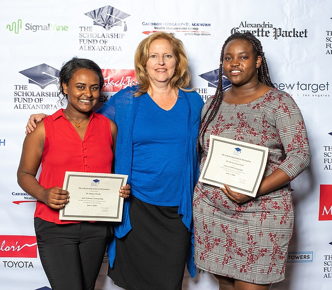 Cindy Anderson, Alexandria School Board chair, presents scholarships to Hannah Woube (left), recipient of the Jack Esformes Scholarship and student keynote speaker Divine Tsasa Nzita (right), recipient of the Class of 1989 Scholarship. Tsasa Nzita will attend Northern Virginia Community College and Woube will attend Virginia Tech.