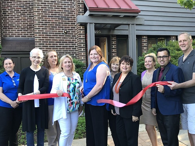With a  snip of her large scissors, Casey White, C.E.O. and Founder of  White H.A.R.T. Massage (center) ceremonially opens her Holistic and Rehabilitation Therapy office in the Town of Herndon. Herndon Vice Mayor Sheila Olem (front center left), Councilmembers Signe Friedrichs and Pradip Dhakal (front center right), and others lend their support.