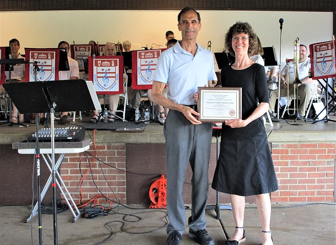 Mount Vernon Community Band Director Linda Davidson, with Mount Vernon District Supervisor Dan Storck, after receiving a plaque of appreciation.