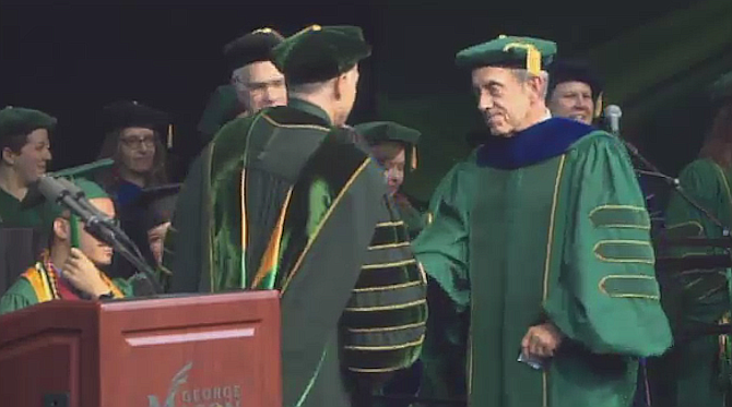 Alexandria Chief of Police Michael Brown, right, is awarded a doctorate degree in Criminology, Law and Society at the George Mason University 2019 spring commencement ceremony at Eagle Bank Arena.