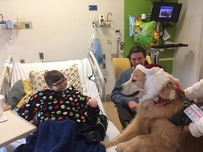 Gavin Smith, shown with his father, Keith Smith, has a visit from a therapy dog. He is wearing a poncho made by his mother, Meg Smith. (December 2016).