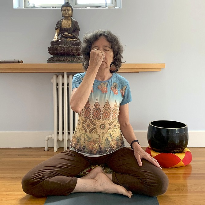 Yoga and meditation teacher Debbie Helfeld practices alternate nostril breathing, which she says can relieve the type of stress that can lead to workplace burnout.